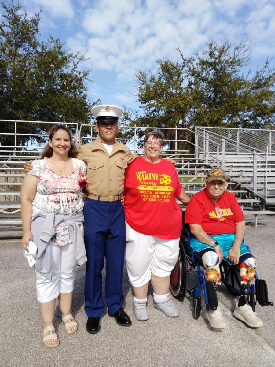 Sandy and Tony, in red, with their daughter Crystal and her son, their grandson Thomas who graduated from Marine Corps Boot Camp in September of 2019.